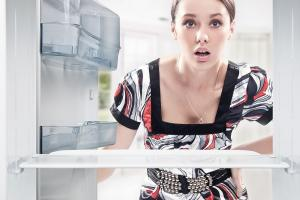 Dziewczyna zaglądająca do lodówki